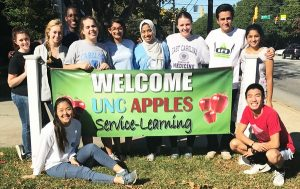 students stand with a banner that reads welcome UNC APPLES service-learning