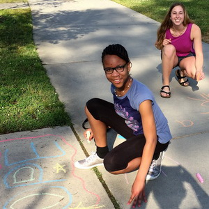 a mentee writes hope in chalk