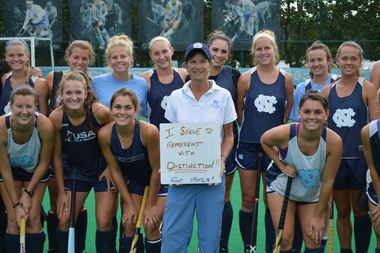 Karen Shelton and the Field Hockey Team Holding Why I Serve Sign