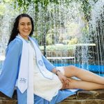 student poses in front of UNC water fountain in graduation gown