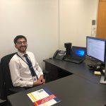 Carolina senior Purshotam Aruwani at his desk in the N.C. Department of Public Safety, during his 2019 APPLES Service-Learning summer internship.