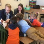 four kids lean toward APPLES student reading for story time