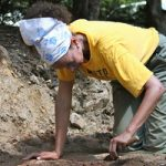 Anna digging with small tool at archaeology site