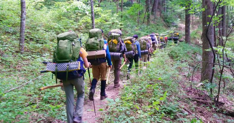Backpackers hiking down a dirt trail