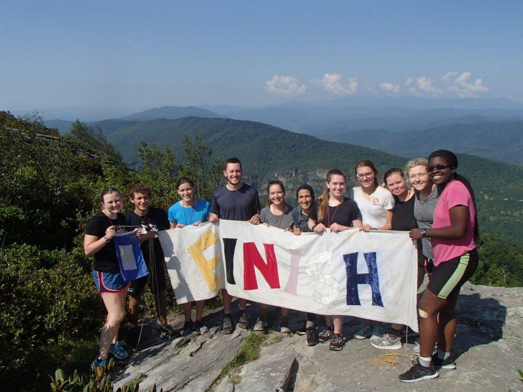 "2019 NCOBS crew holding ""finish"" banner"