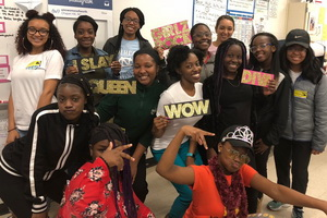 group of young women of color holding signs with message of empowerment
