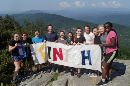 group of UNC students in outward bound hold a finish sign on top a mountain