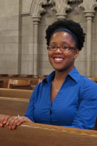 Kennetra Irby poses while sitting in a church pew