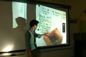 Ryan Lei points to contents displayed on an overhead projector in a classroom