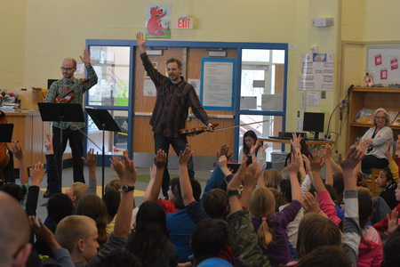 Arts Fellows with fiddles stand before classroom of school children all raising their hands