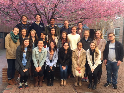 Philanthropy class poses in front of budding tress with pink flowers