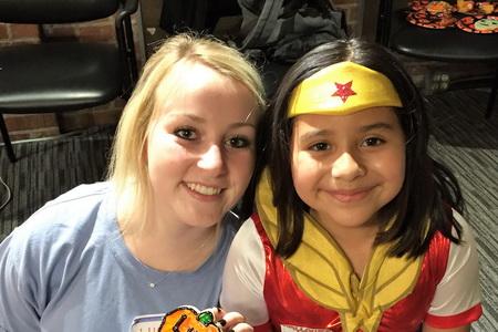 female UNC student mentors child wearing a wonder woman costume