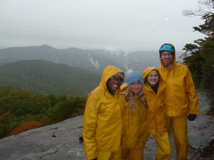 Community Service Scholars in matching yellow rain suits, with misty mountains behind them