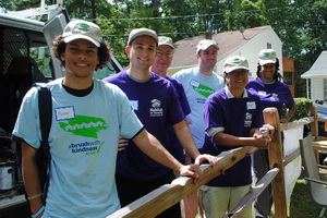 Five students standing by fence at Habitat for Humanity work site