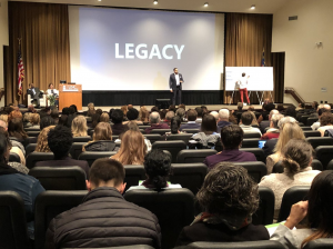 """A man speaks to a crowded auditorium. Behind him, a large screen displays the word """"legacy."""" Near him onstage, a person facing a white poster is transcribing the speaker's ideas into art."""