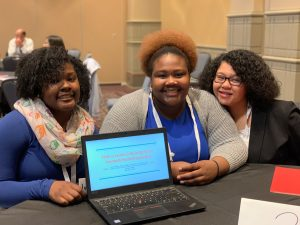 Three young women smile in front of an open laptop