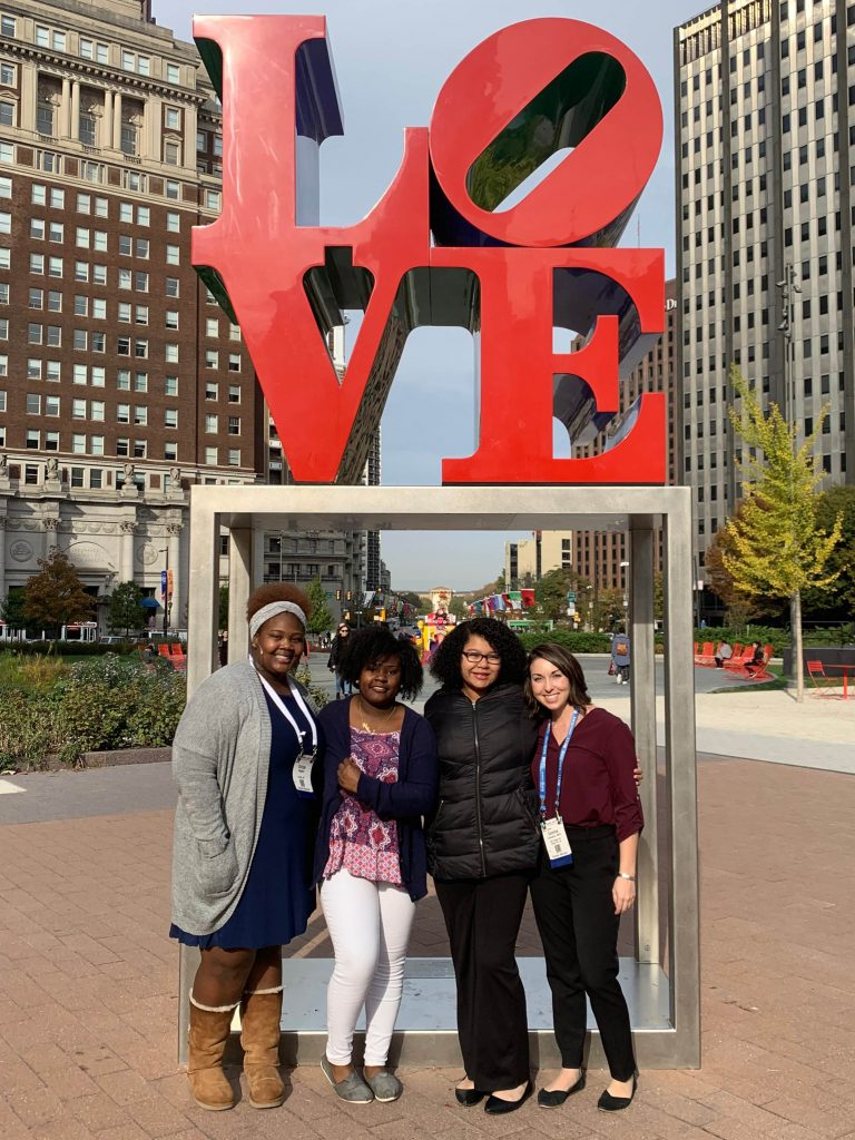 Four young women stand in front of the iconic red LOVE sculpture in Philadelphia