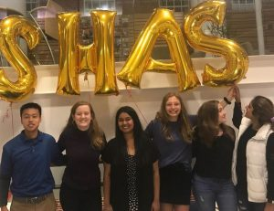 A group of students standing and smiling in front of large gold balloons in the shape of letters spelling SHAS