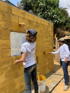 Jesse LaMasse paints a yellow cinderblock structure in Guatemala.