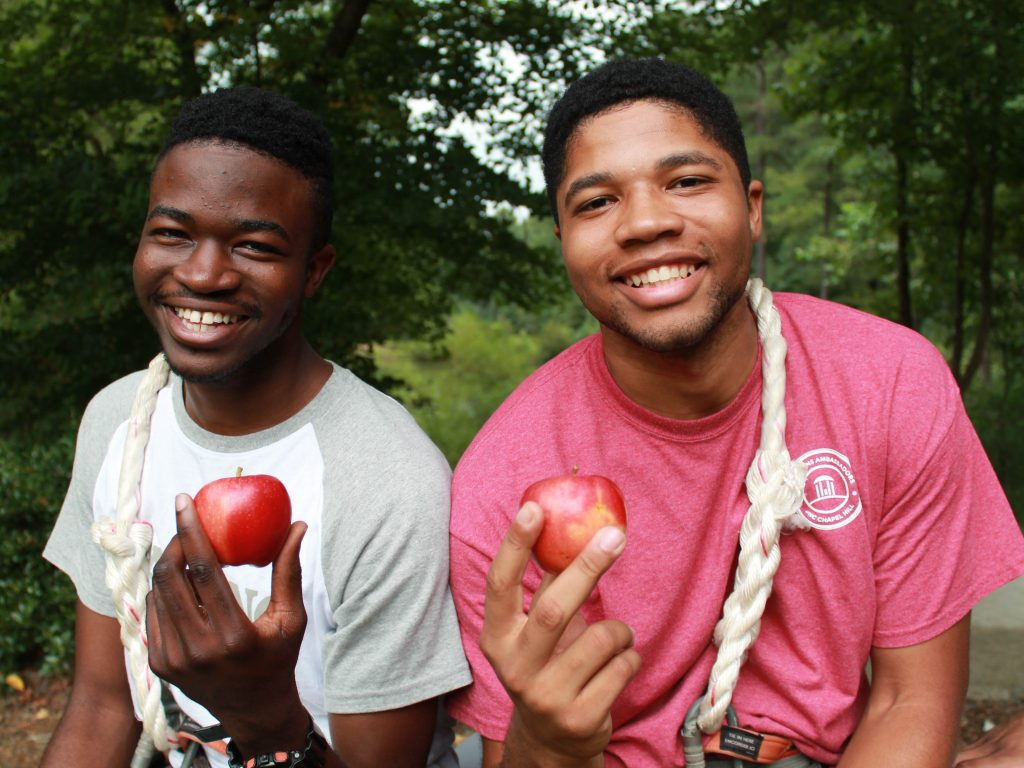 two young men on a ropes course smile and hold up red apples