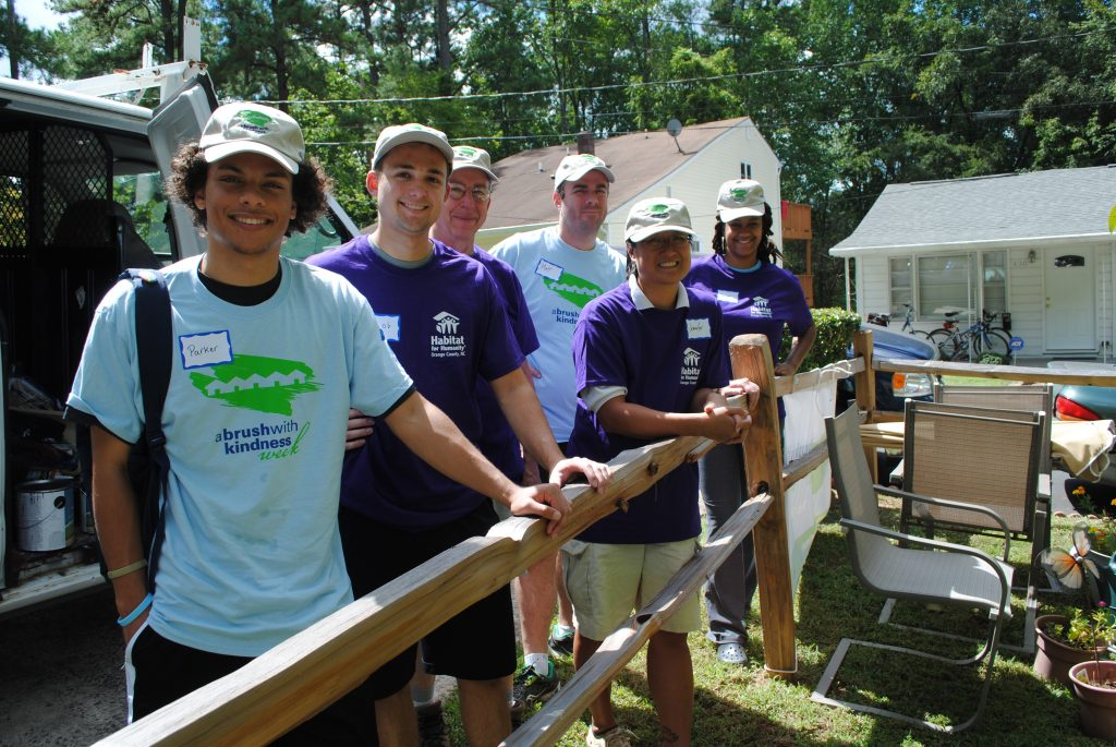 Service Learning Course Students Smile with Habitat for Humanity Community Partners at a Buildsite
